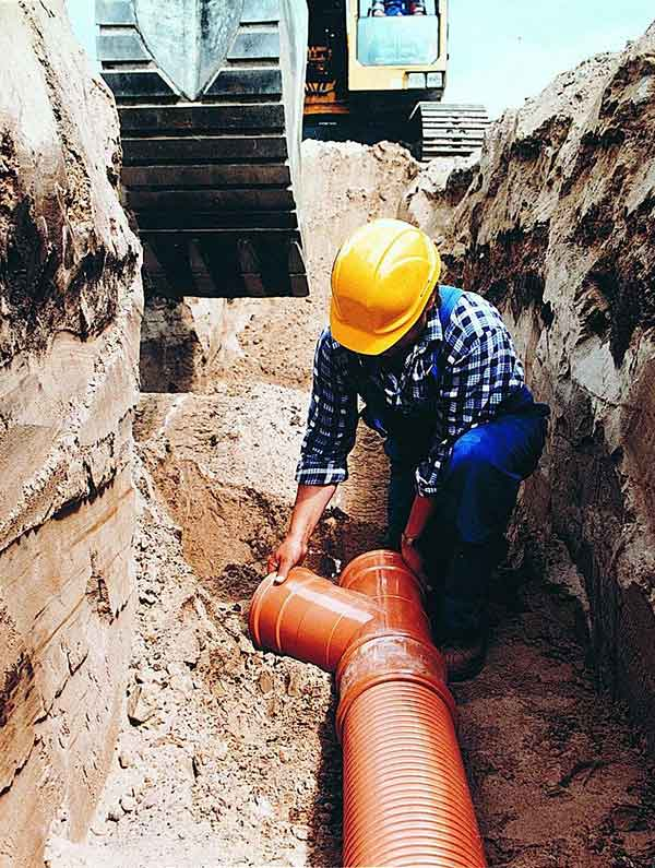 Man laying pipe made of polyvinyl chloride, or PVC