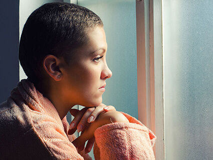 Young woman in a robe looking out a window