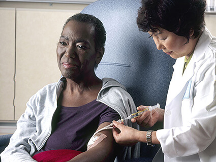 A female nurse administers chemotherapy to a woman through a catheter in her left arm.