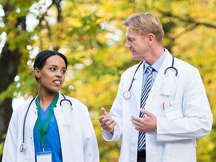 A male and female doctor walking outside and talking.
