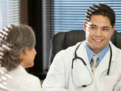 A young male doctor talking with an older female doctor.