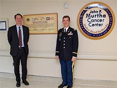 Dr. Norman Sharpless and Colonel Craog Shriver standing in front of a sign for the Murtha Cancer Center