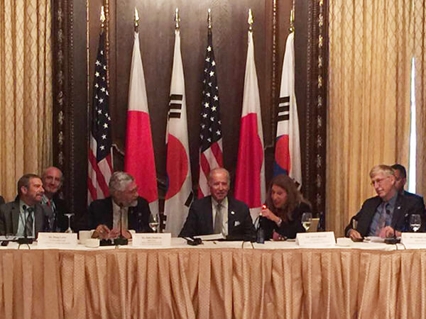 A group of people sitting at a table in front of the flags of the United States, Japan, and Korea