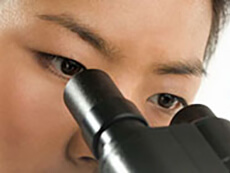 An Asian woman looks into a microscope.