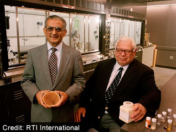 Photo of Mansukh Wani, Ph.D., and Monroe Wall, Ph.D., in a laboratory holding a sample of bark from the Pacific yew tree.