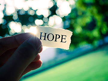 Photo of a hand holding a small piece of paper with the word hope.