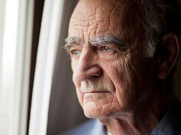 Un hombre de edad mira hacia el frente.