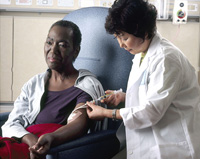 A nurse administers chemotherapy to an elderly patient
