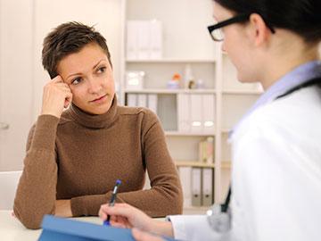 Una mujer preocupada habla con su doctora