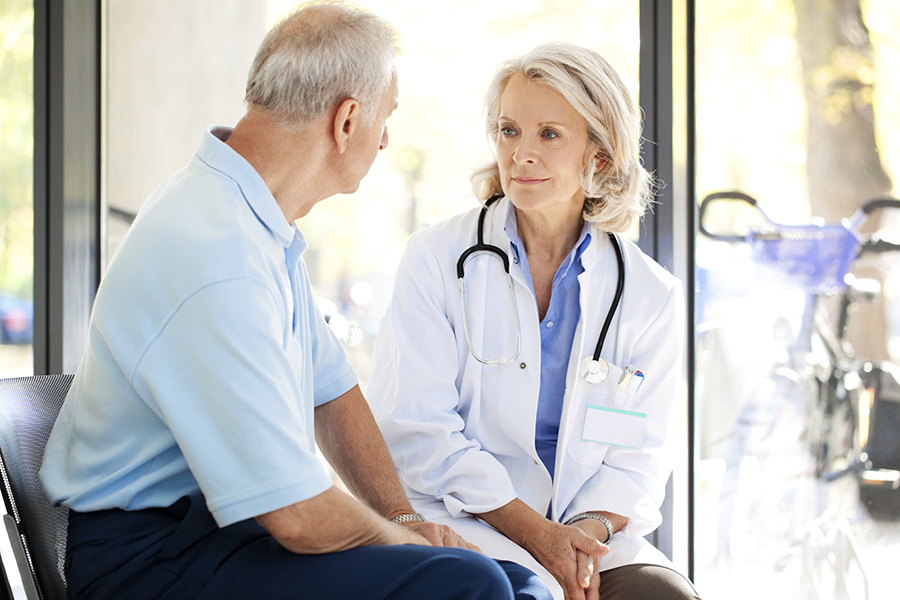 Elderly male patient talking with female doctor
