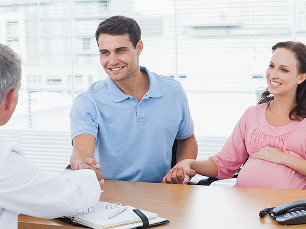 Una mujer embarazada y su esposo en una cita médica.