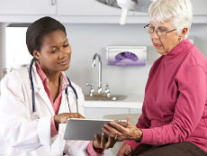 A Female Doctor Talking with a Female Patient Reviewing an iPad