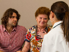 A Hispanic woman and adult son talking with a female doctor