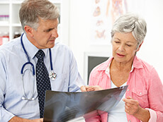 Male Doctor Talking with an Elderly Female Patient About a Digital Image