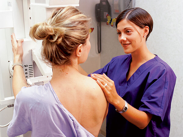 A woman talking with a female technician while getting a mammogram