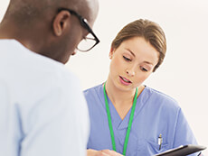 A female nurse shows a male patient an Ipad