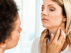 Young woman receiving thyroid exam from her doctor