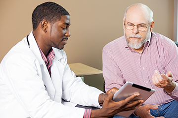 Young Doctor Showing An Older Male Patient Information on an iPad