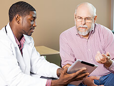 Young doctor showing older man something on an tablet computer