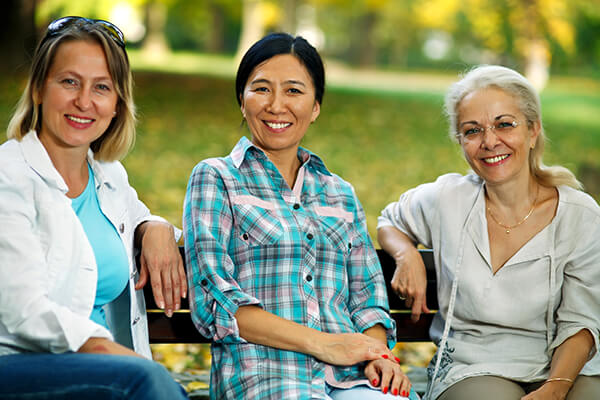 3 women sitting on a park bench