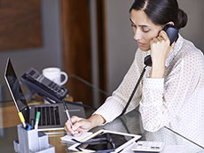 Woman at a desk talking on a phone