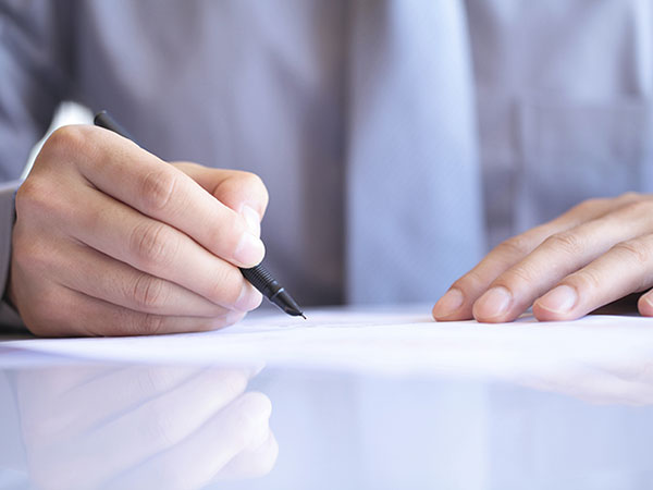 A hand holding a pen is signing a paper