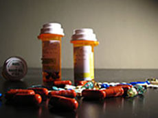 Two prescription bottles standing up and one laying down with a variety of tablets and capules surrounding the bottles.