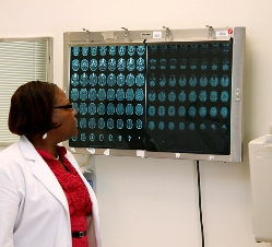 An African-American female nurse practitioner in white coat reviews films on light board from a CT scan of the brain in an examination room of a clinic