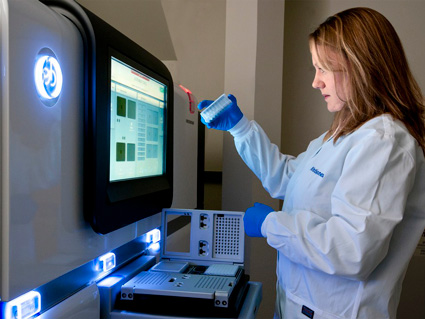 A female technician working at a genomic sequencing machine.