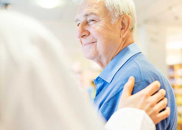 A doctor puts his hand on an older man's shoulder.