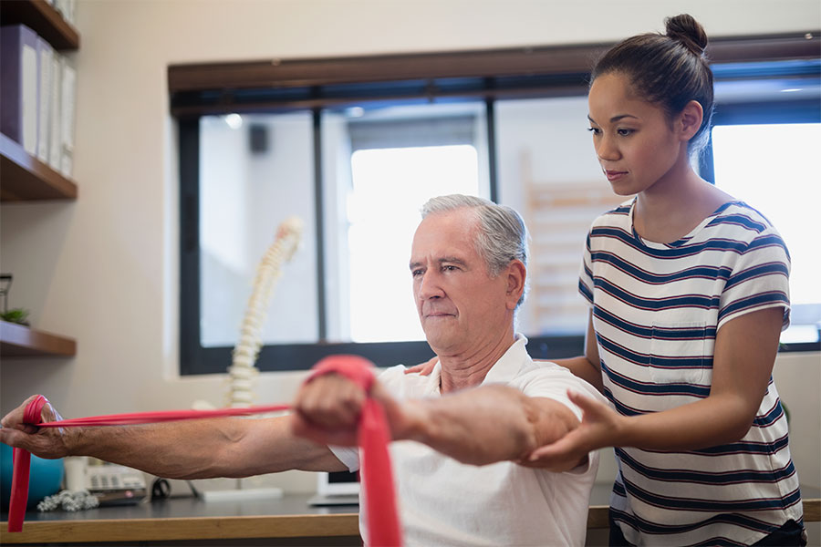 An older man performing rehab with an exercise band.