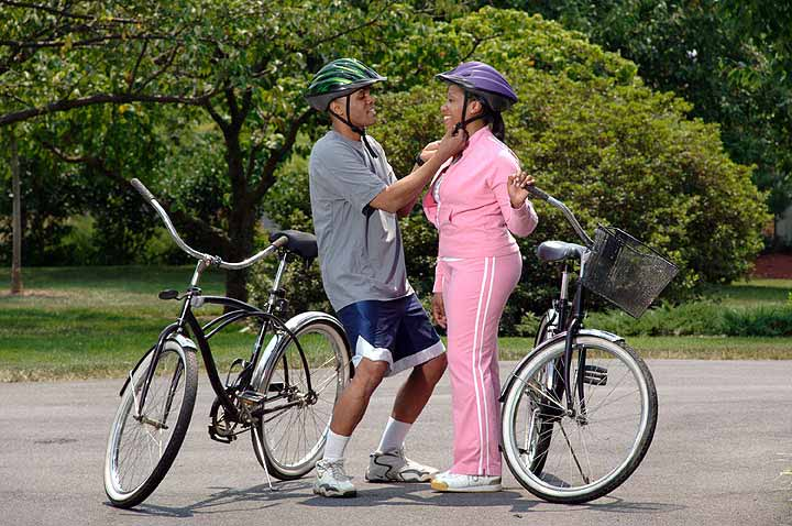 An African-American man adjusts an African-American woman's helmet strap as they prepare for a bicycle ride.