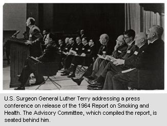 In this Black & White photo, the U.S. Surgeon General, Luther Terry, is standing at a podium, addressing a non-pictured audience.  Two rows of men are seated in folding chairs behind him.
