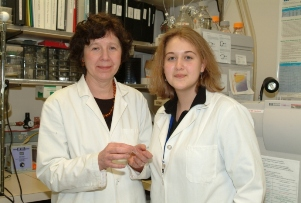 Two women in white lab coats in a research lab pose in front of lab equipment.