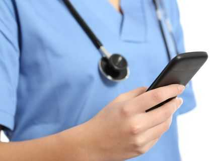 Health care provider looking at a smartphone