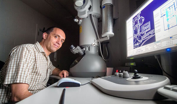 Researcher working with an electron microscope