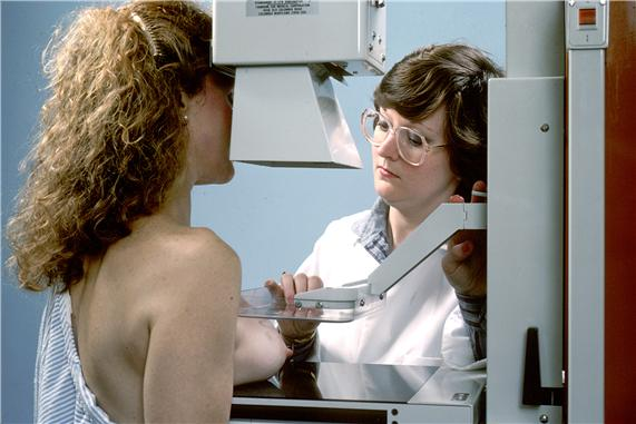 Photograph shows the right breast positioned between the plates of a mammography machine.