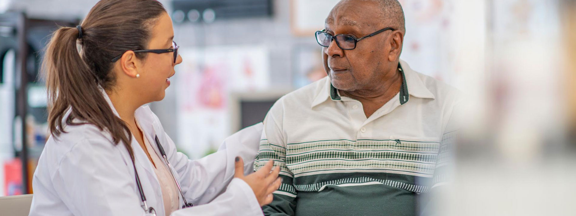 Female medical professional and older black man conversing.