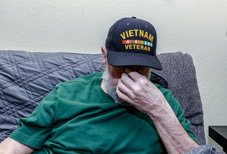 A depressed Vietnam War USA military veteran has his head down while covering his face with his hand