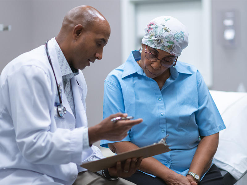 Older African-American woman in consultation with a doctor.