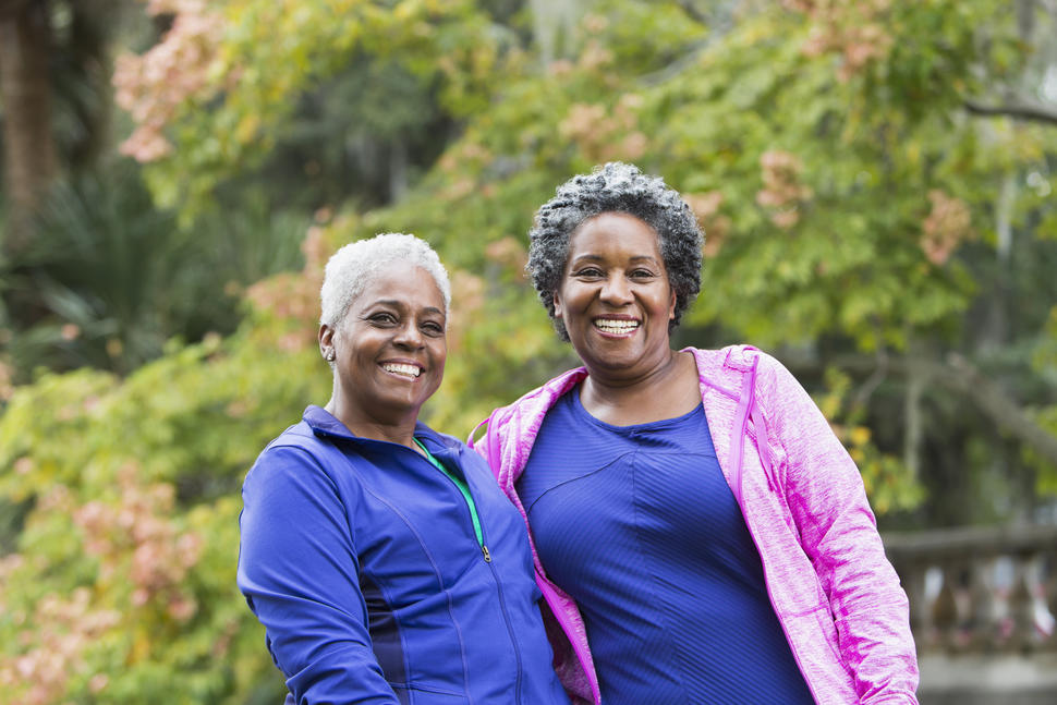 2 middle-aged women in a park pose for the camera