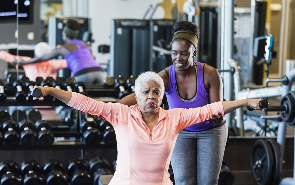 Older African-American woman lifting weights in a gym