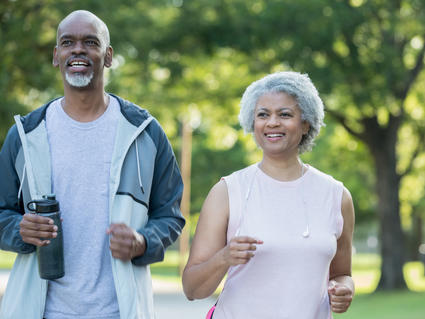 An older African American couple walking in a park.