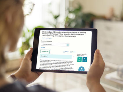 Woman holding a tablet showing a clinical trial summary