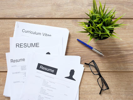 Resume papers on table with plant and reading glasses