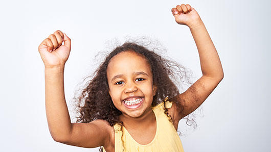 A young girl with long, curl dark hair and yellow dress smiles with her arms raised up.