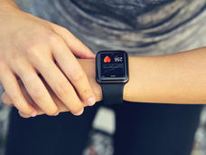 A young woman checks her heart rate on a smartwatch wearable device.